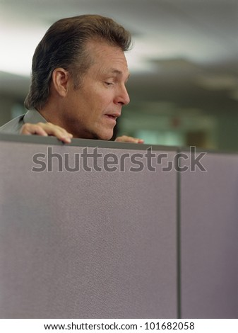 Businessman looking over cubicle wall - stock photo