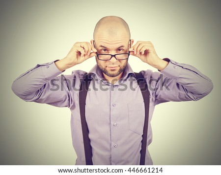 Businessman looking over glasses.bald man in a purple shirt looking through glasses. - stock photo