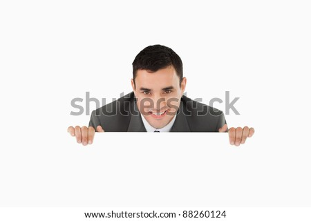 Businessman looking over wall against a white background