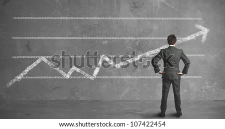 Businessman looking the company trend in the wall - stock photo