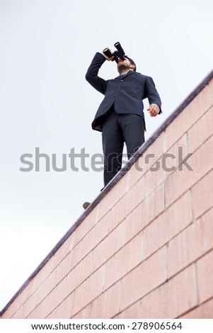 Businessman looking thought his binoculars - stock photo