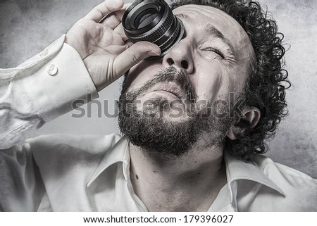 Businessman looking through a lens, man in white shirt with funny expressions