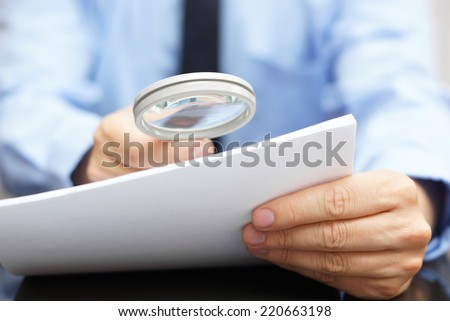 Businessman looking through a magnifying glass to contract - stock photo