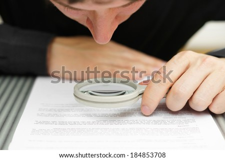 Businessman looking through a magnifying glass to document - stock photo