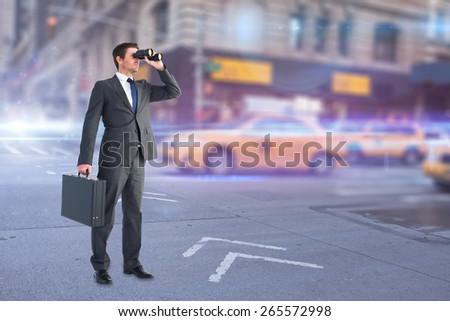 Businessman looking through binoculars against blurred new york street - stock photo