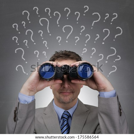 Businessman looking through binoculars searching for answers in front of question marks written on blackboard - stock photo