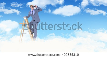 Businessman looking through binoculars while standing on ladder against blue sky - stock photo