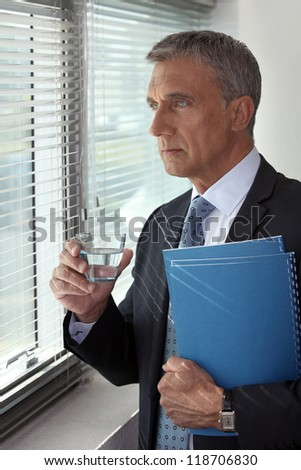 Businessman looking through his office window - stock photo