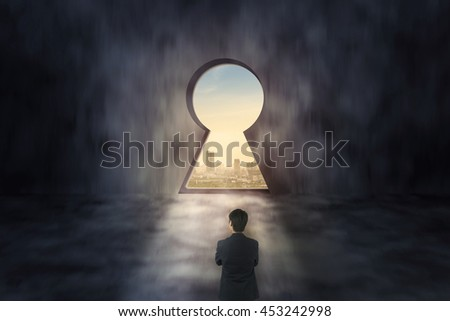Businessman looking through keyhole , business concept