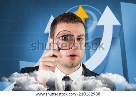Businessman looking through magnifying glass against digital blue background with arrows - stock photo