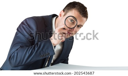 Businessman looking through magnifying glass on white background