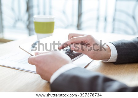 businessman looking through news on tablet - stock photo
