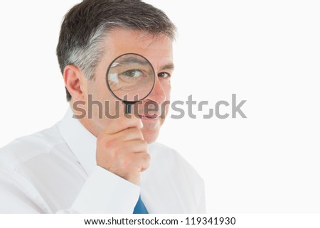 Businessman looking through small magnifying glass and smiling