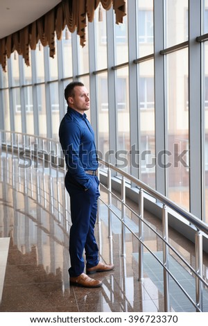 businessman looking through the phone by the window