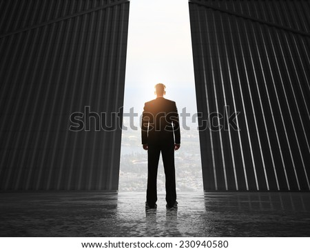 businessman looking to open doors to hangar - stock photo