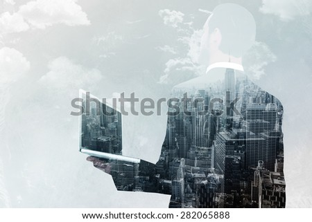 Businessman looking up holding laptop against new york skyline - stock photo