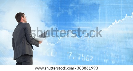 Businessman looking up holding laptop against stocks and shares