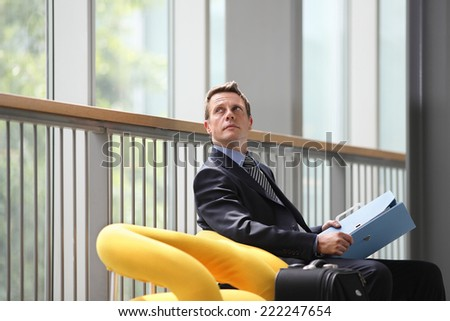 businessman looking up with blue folder in her hand sitting in the waiting room - stock photo