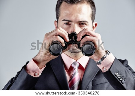 Businessman looking with binocular isolated over grey - stock photo