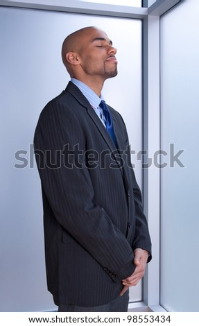 Businessman looking zen, standing with his eyes closed near a window. - stock photo