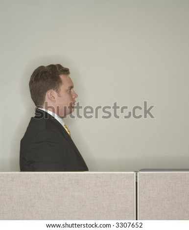 Businessman looks ahead and stares away from the camera as he gives his profile standing behind the office cubicle wall