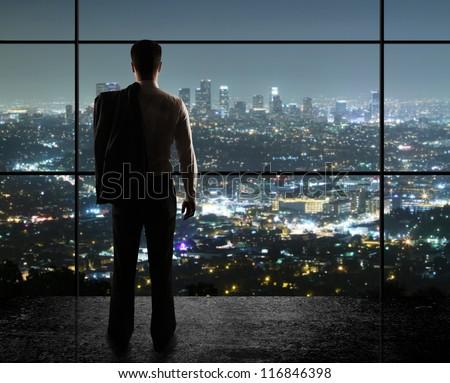 businessman looks in night city - stock photo