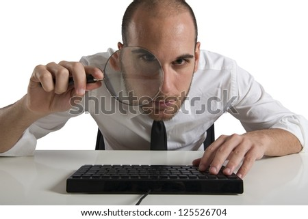 Businessman  looks on the computer with a magnifying glass - stock photo
