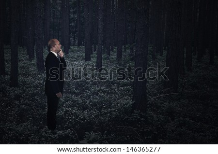 Businessman lost in a dark creepy forest at midnight