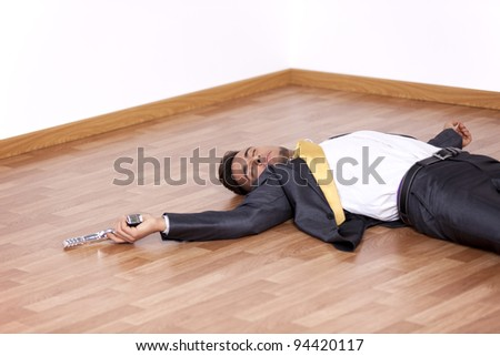 Businessman lying dead in the office floor with a gun in his hand