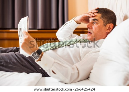 Businessman lying in bed and reading bad news in newspaper - stock photo