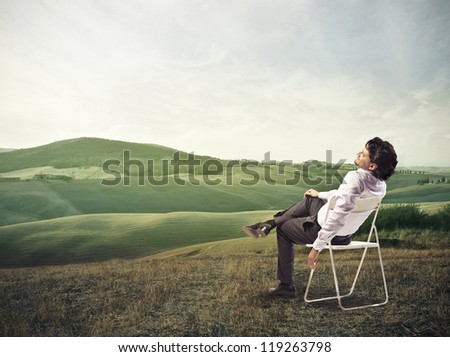 Businessman lying on a chair in a beautiful landscape