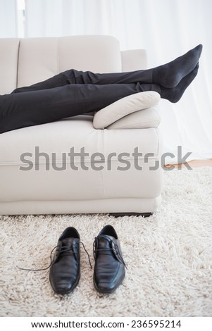 Businessman lying on couch legs only visible at home in the living room - stock photo