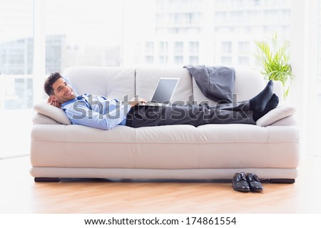 Businessman lying on sofa using his laptop smiling at camera in the office - stock photo