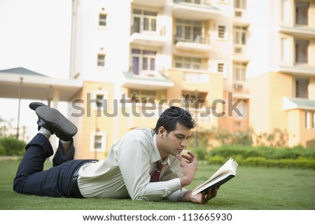 Businessman lying on the grass and reading a book - stock photo