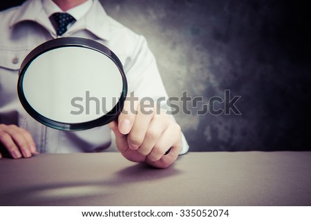 Businessman, magnifying glass - stock photo