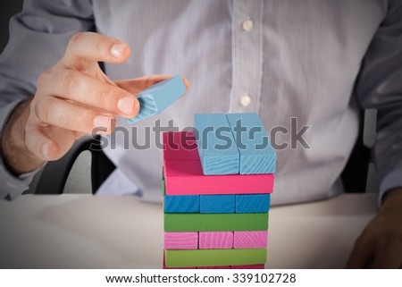 Businessman make a building with wood blocks - stock photo