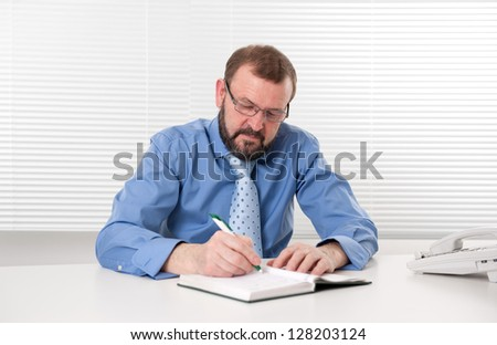 businessman makes a note in notebook - stock photo