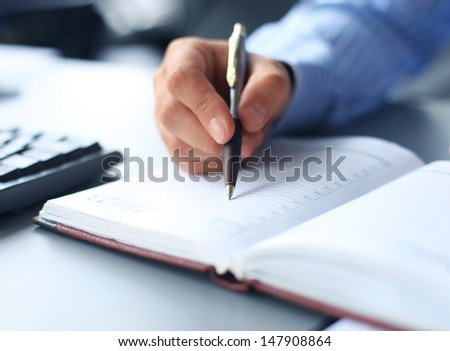 Businessman makes a note in notebook.