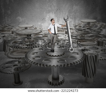 Businessman makes maintenance of a system of gears