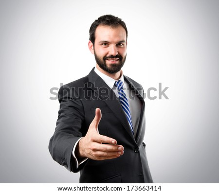businessman making a deal over grey background  - stock photo