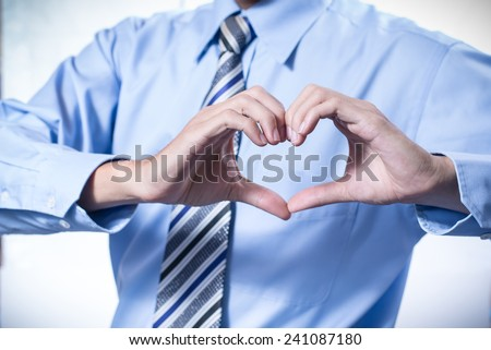 Businessman making a heart with her hands over white background, I love business - stock photo