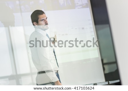 Businessman making a presentation in front of whiteboard. Business executive delivering a presentation to his colleagues during meeting or in-house business training.  - stock photo