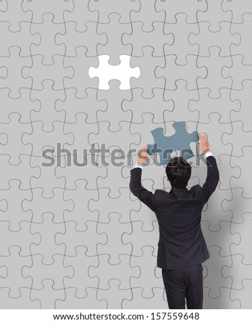 Businessman making a puzzle on the wall - stock photo