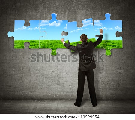Businessman making a puzzle on the wall with  picture of nature - stock photo
