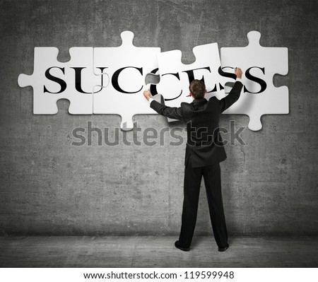 Businessman making a puzzle on the wall with the word Success - stock photo