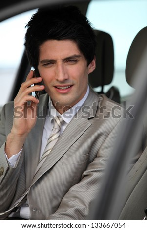 Businessman making call from parked car - stock photo