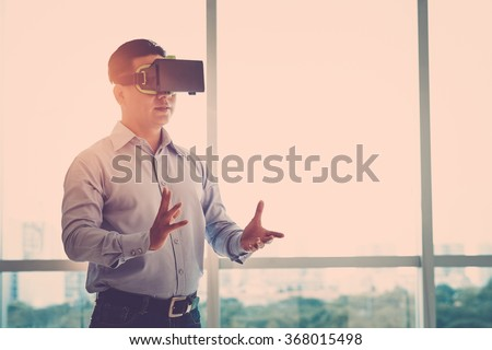 Businessman making gestures when wearing virtual reality goggles - stock photo