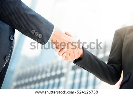 Businessman making handshake with a businesswoman in blur building background - greeting , dealing, merger and acquisition concepts