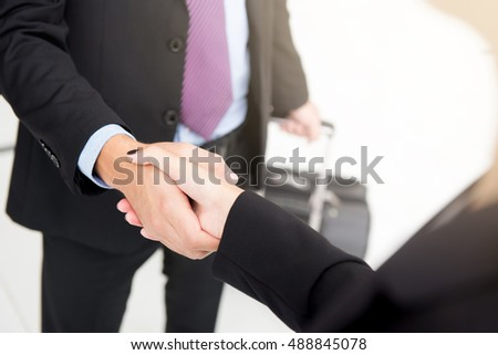 Businessman making handshake with a businesswoman while holding baggage in another hand at the airport, business travel concept