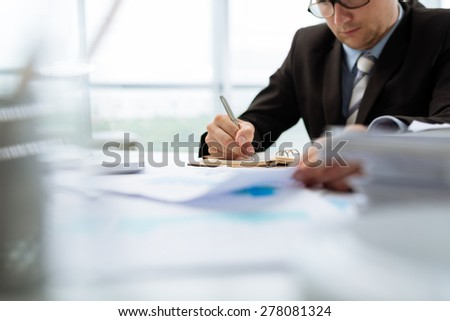 Businessman making notes in his notepad, selective focus - stock photo